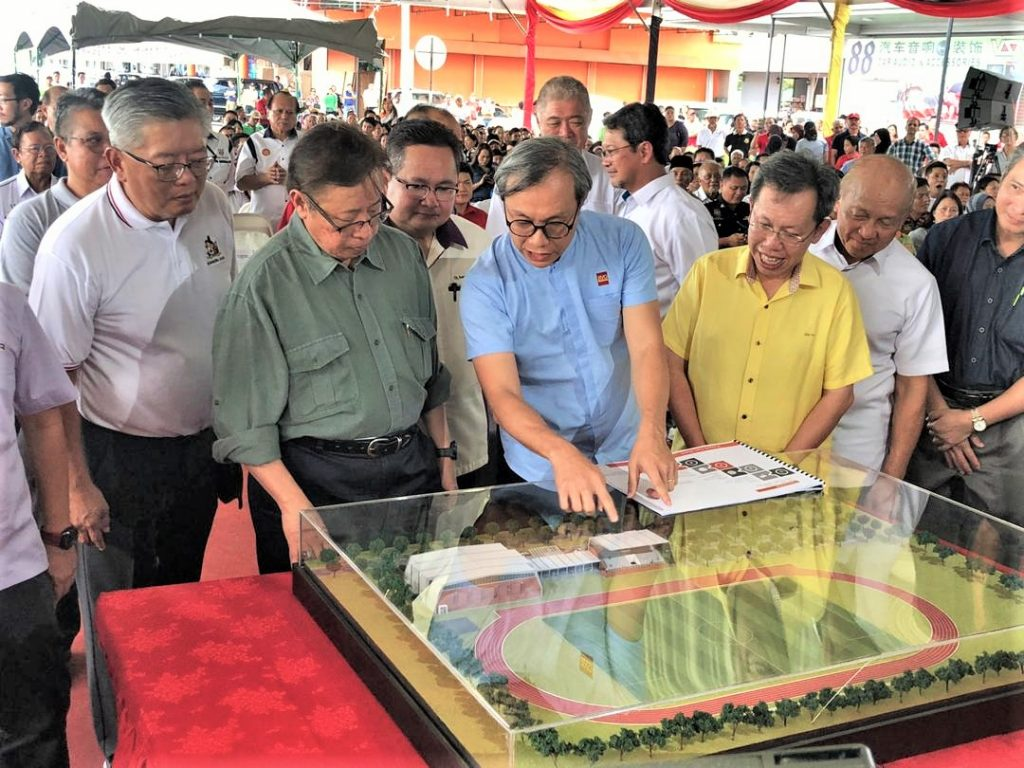 Abang Johari (second left) looks closely at a model of the proposed community sports centre.